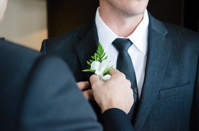 白い花をつけるスーツの男